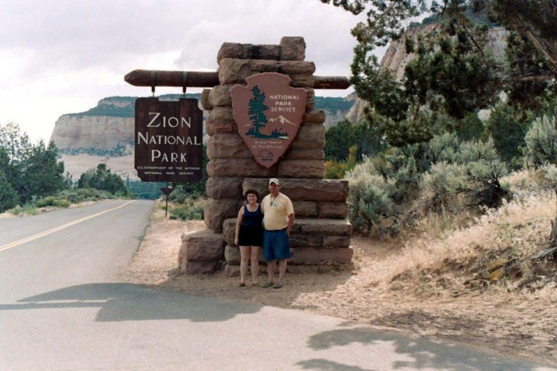 Standing in front of the sign for Zion, another US National Park
