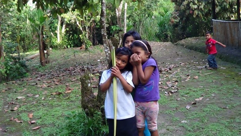Four children from the Kichwa Amazon tribe. One girl whispers to another friend while another girl stands behind. Young boy tries to act up in the background