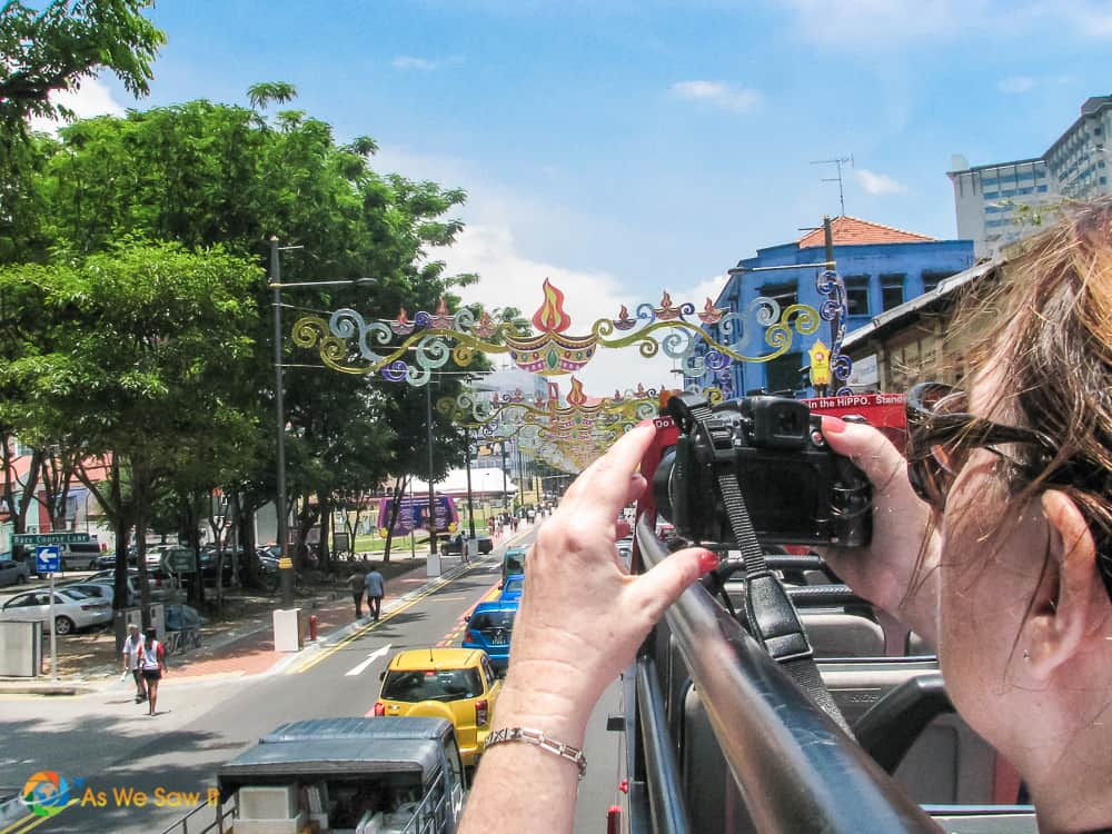 woman taking photos from top of sightseeing bus