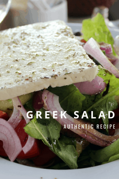 closeup of a bowl of Greek salad with slab of feta cheese. text overlay says Greek salad authentic recipe.