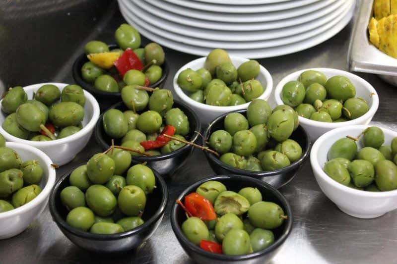 Tray of tapas full of small bowls of green olives, ready for serving, along with stack of plates in background
