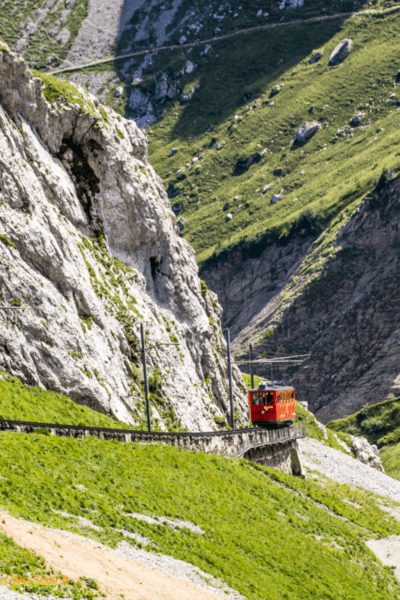 Red train goes down the track on Mount Pilatus.