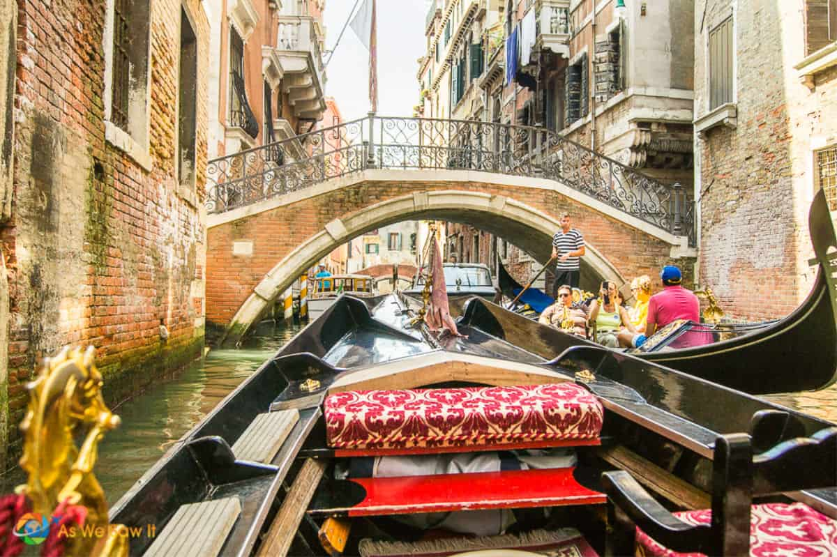 Front of Venetian gondola, as seen by passenger. Bridge and oncoming gondola in background