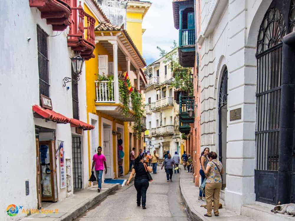 Buildings line a narrow street in Cartagena. People in the street.