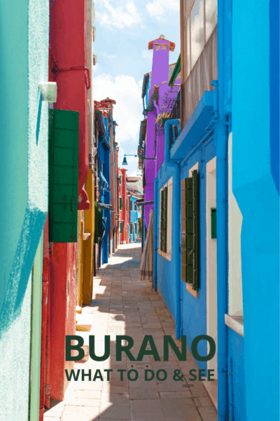 Colorful houses line a sidewalk in Burano Italy. Text overlay says Burano What to See & Do