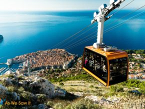 Orange cable car rises to top of Mount Srd. View of Dubrovnik and Adriatic sea in background.