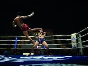 muay thai fighter deals an airborne kick in a Bangkok stadium