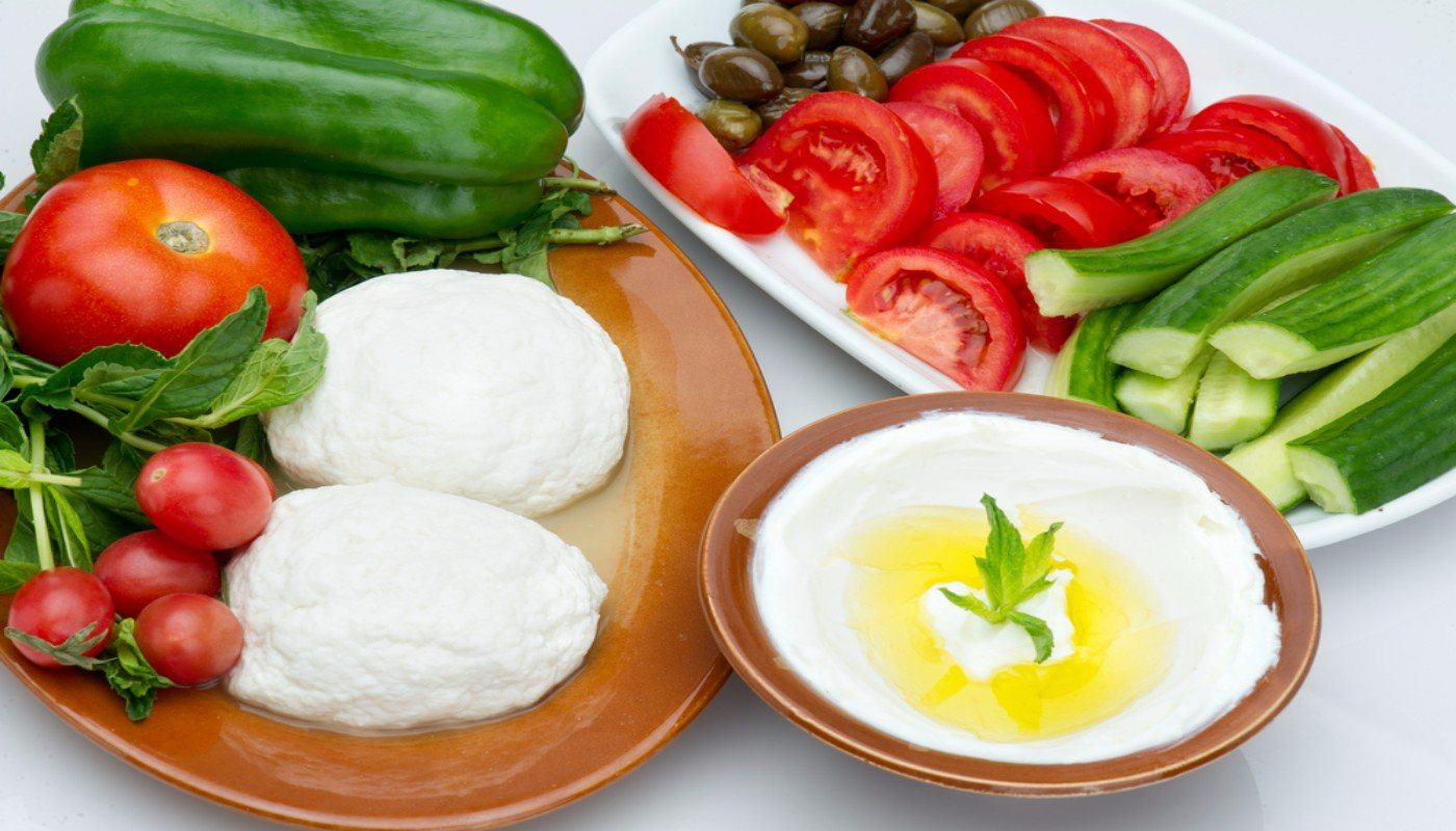 Bowl of Labneh surrounded by a platter and cutting board with cucumbers, herbs, radishes, olives and tomatoes.