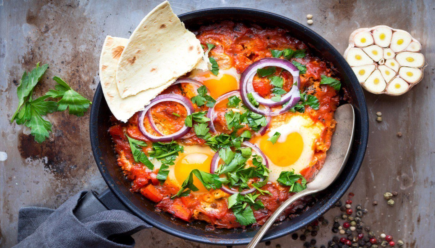 Skillet with Shakshuka, topped with a couple of pieces of flatbread.