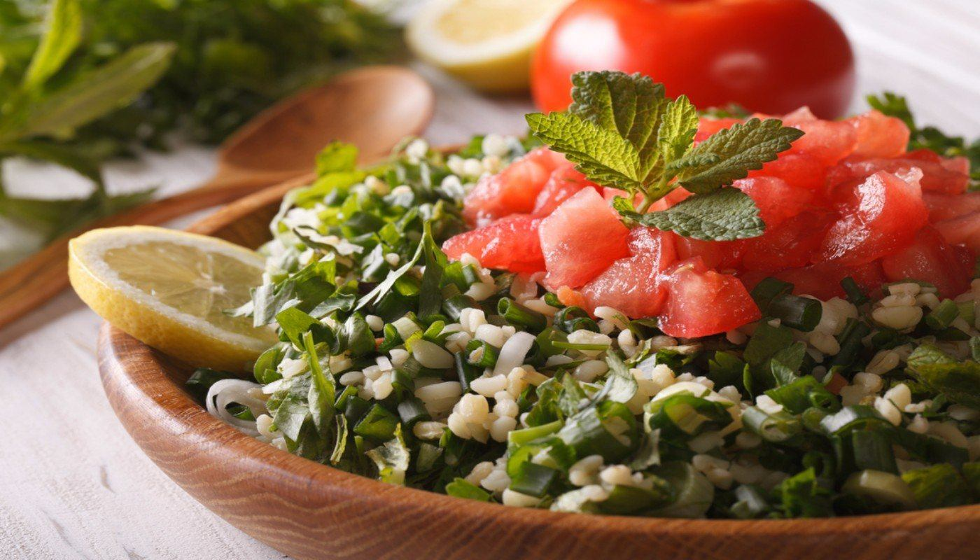 Bowl of tabouleh topped with tomatoes and a sprig of mint and garnished with a slice of lemon. Tomato in background.