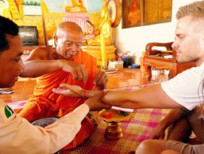 Seated saffron-robed monk tying a cord around a man's wrist.
