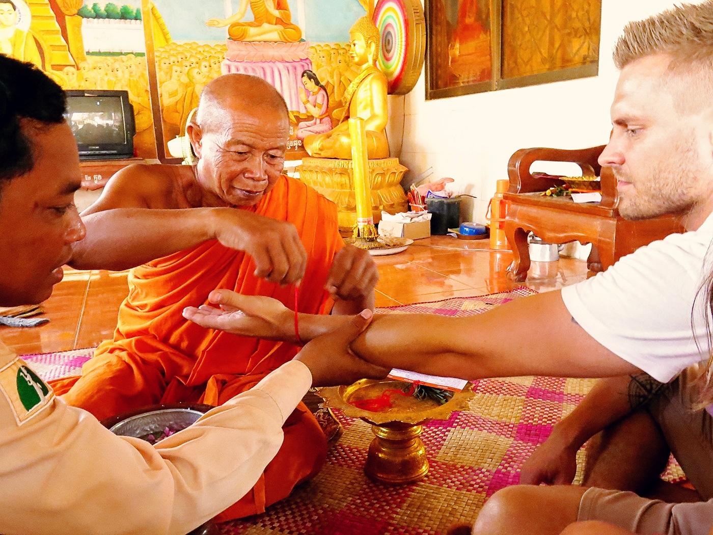 Seated saffron-robed monk tying a cord around a man's wrist.