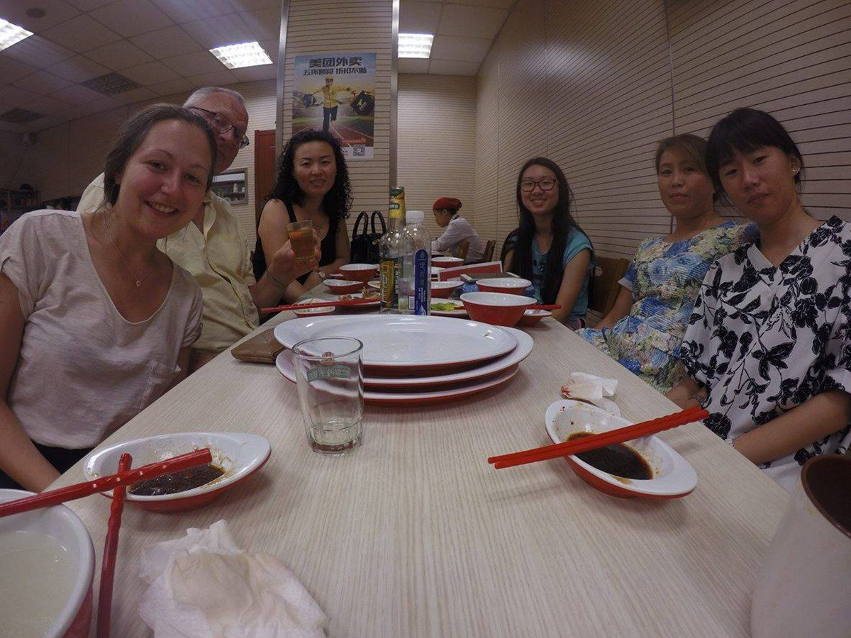 author sits with Chinese people at long table after dinner