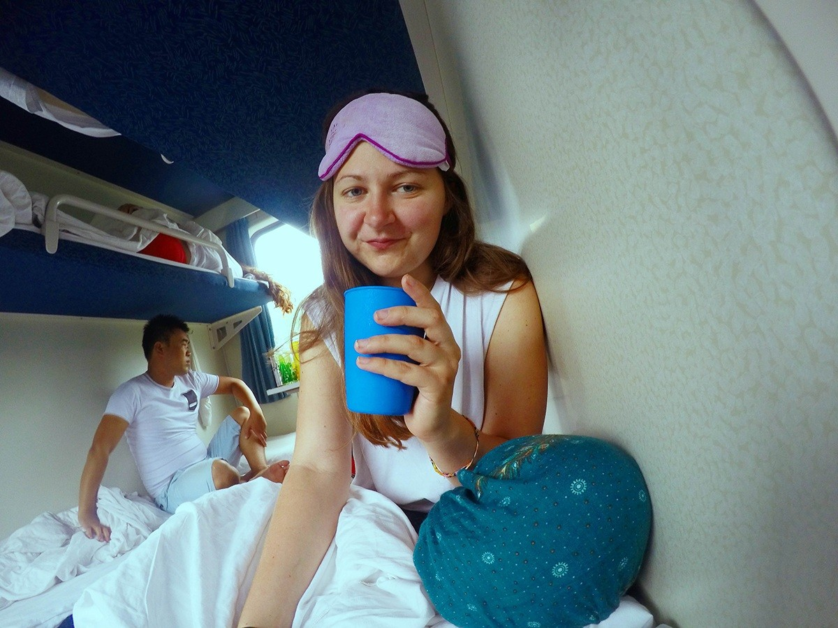 selfie of author on a train bunk holding a blue plastic cup and wearing a sleep mask