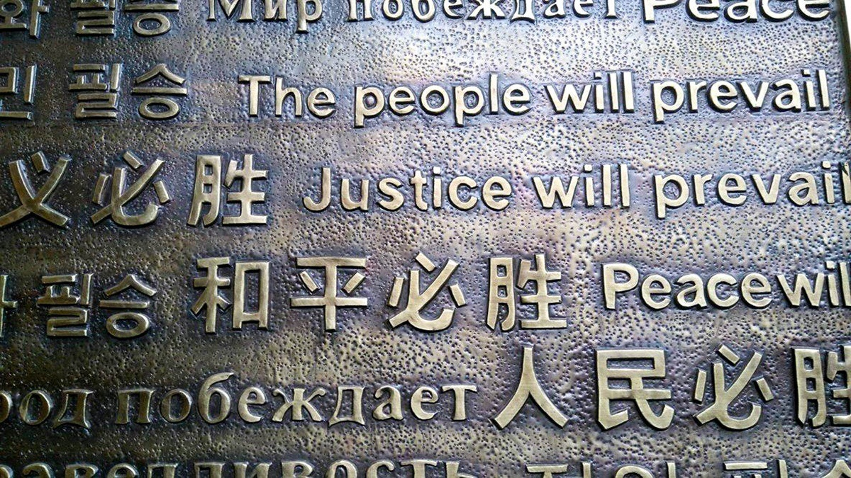 Multilingual metal sign says The People will prevail, justicde will prevail and Peace will prevail
