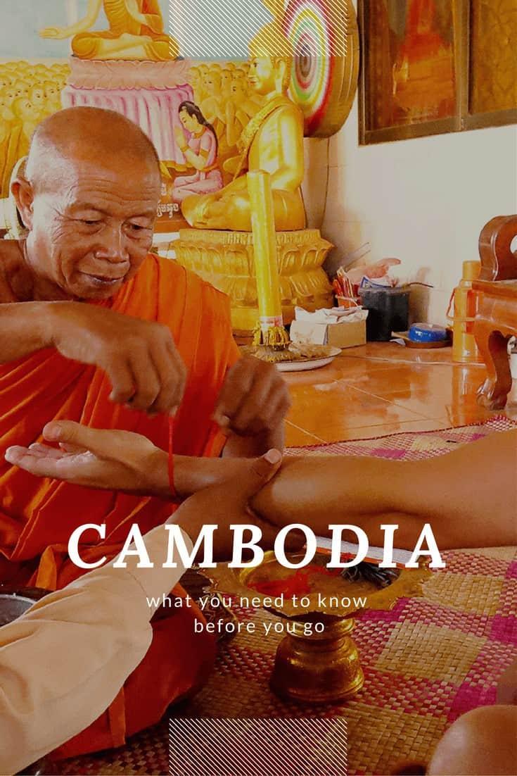 khmer monk tying red thread around someone's wrist