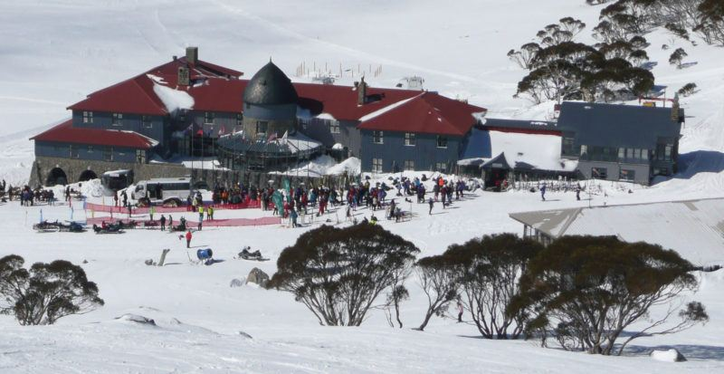 Grey ski lodge with red roof at Charlotte Pass, one of Australia's best ski slopes.