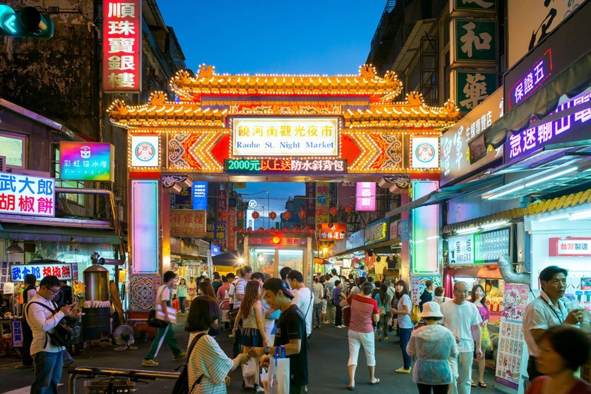 Visitors along a roadway that runs under a gate in Raohe Street Night Market. Night markets are.one of the best places in Taiwan to visit for tourists