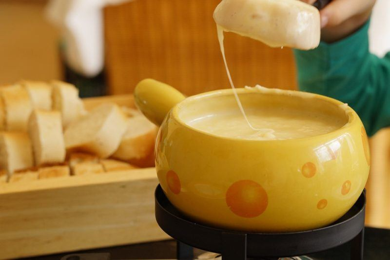 Bread dripping a string of cheese above a pot of Swiss fondue.