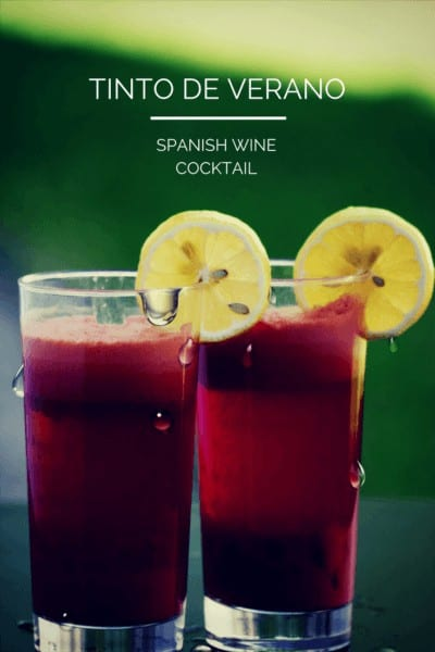 Two glasses of red tinto de verano with lemon garnish on green background. Text overlay says Tinto de Verano Spanish Wine Cocktail