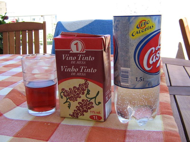 Small juice glass, box of Spanish red table wine, and bottle of La Casera, on a picnic table with red tablecloth.