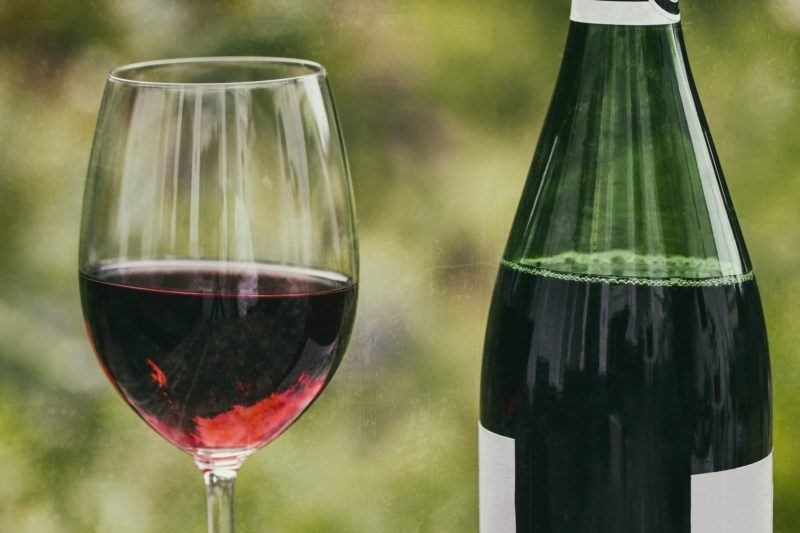 Closeup of a glass of red wine and a bottle of red wine