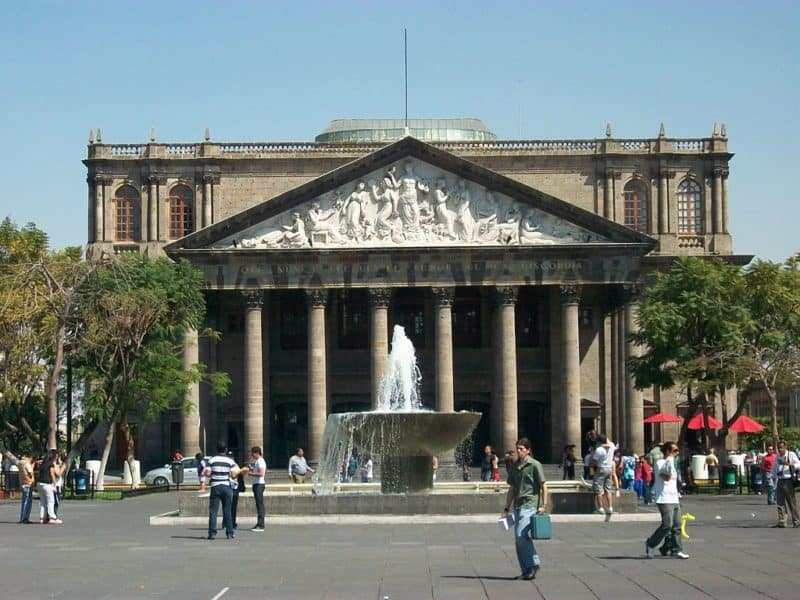 Facade of Guadalajara's Degollado Theater has carvings above its pillars. Fountain in front.