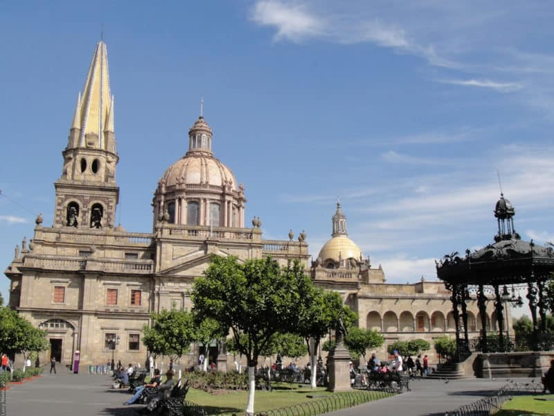 Large domed building fronted by park and tree in Guadalajara Mexico