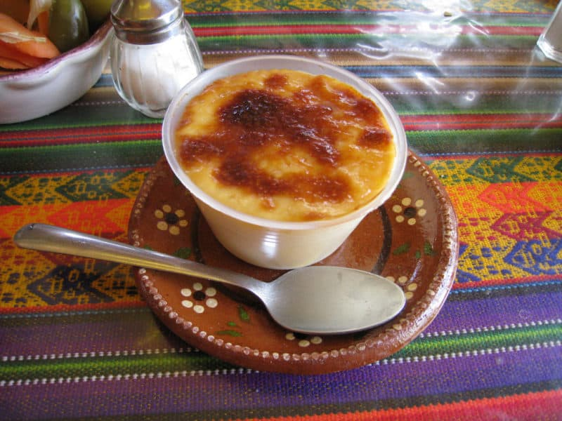 Jericalla flan with toasted top, in cup on plate with spoon