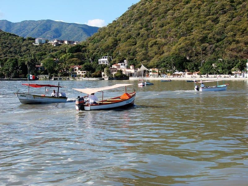 Small motorboats on lake with beach, shops and wooded hills in the background.