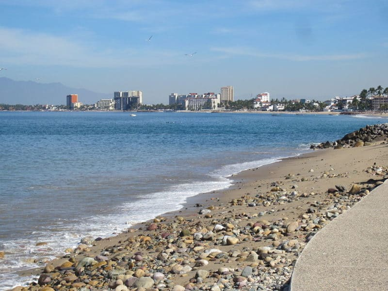 Calm ocean waves with puerto vallarta cityscape in background, as seen fron the esplanade.