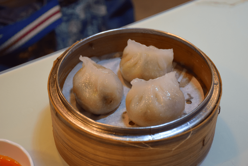 Bamboo tray holding three steamed dim sum, one of the most traditional foods in hong kong
