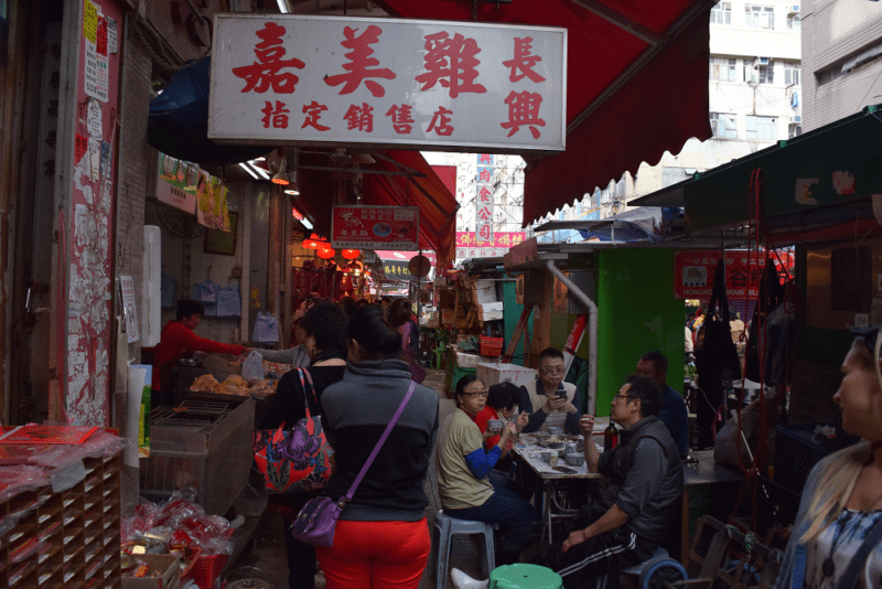 Crowded alleyway in Hong Kong full of street food vendors and tables
