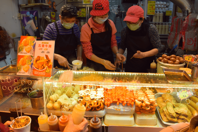 Three staff wear surgical masks as they skewer fish balls behind a counter of food in a Hong Kong restaurant