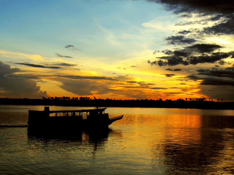 brilliant sunset silhouettes a boat on the Amazon River
