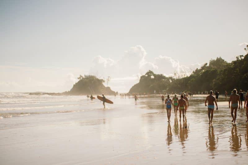 Surfers on the beach at Byron Bay