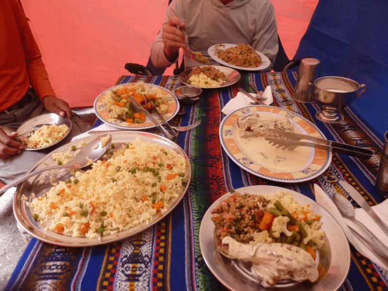 Dinner while hiking the Inca Trail is chicken in creamy sauce, a vegetable medley, quinoa and rice, Plates of food on a striped tablecloth.