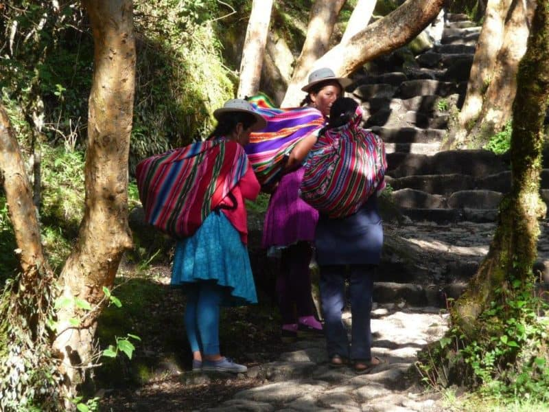 3 Peruvian women in hats carry large colorful bags.over their shoulders