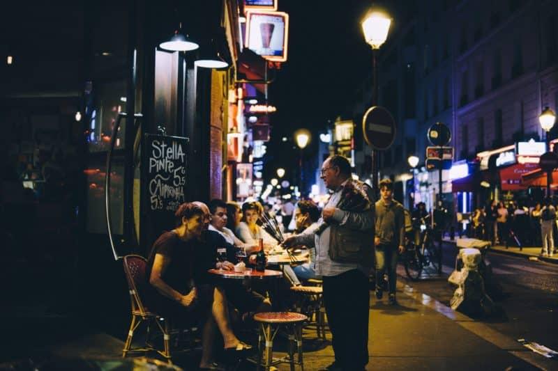Patrons sit at sidewalk tables enjoying the nightlife