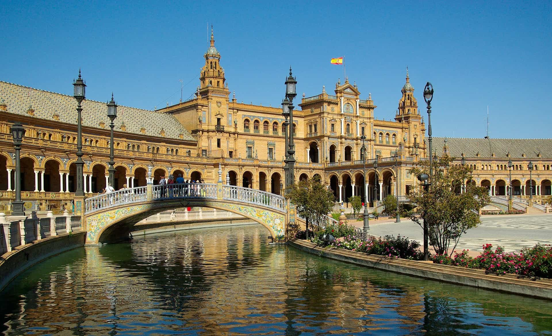 Seville is one of the best reasons to visit the south of Spain. Here, a river and bridge in Plaza de Espana with brick building in background. Spain's flag is flying from the roof.