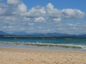 Kayakers on Byron Bay as seen from beach with hills in background