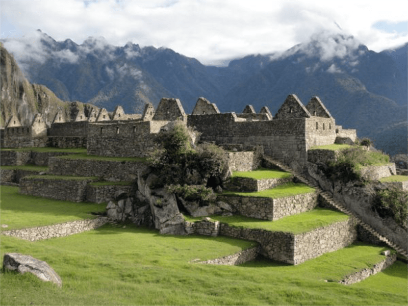 Machu Picchu ruins and walled rock terraces and low-hanging clouds overhead