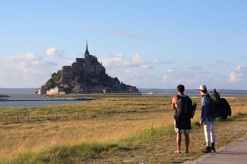 Two backpackers in foreground looking at Mont Saiint-Michel. Grass and water between them.