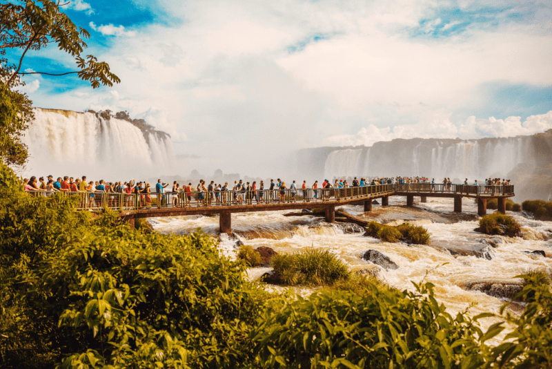 crowds of people stand on walkway over the water coming from Iguazu Falls in the background
