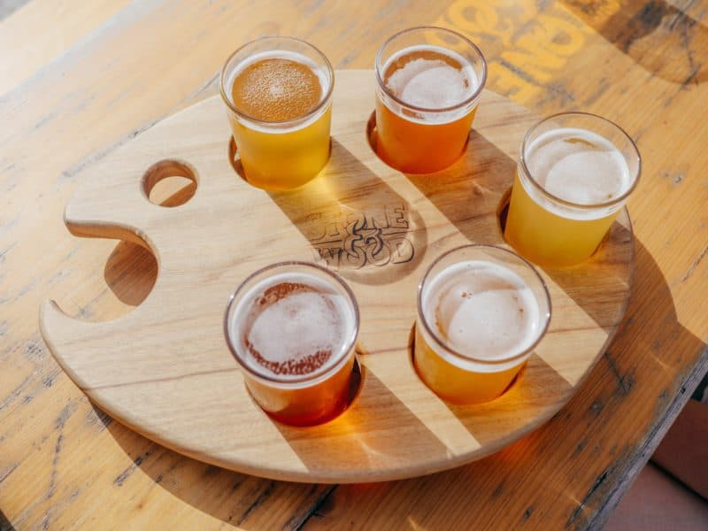 a wood palette holds a flight of 5 beers at Stone & Wood Brewing Company in Byron Bay