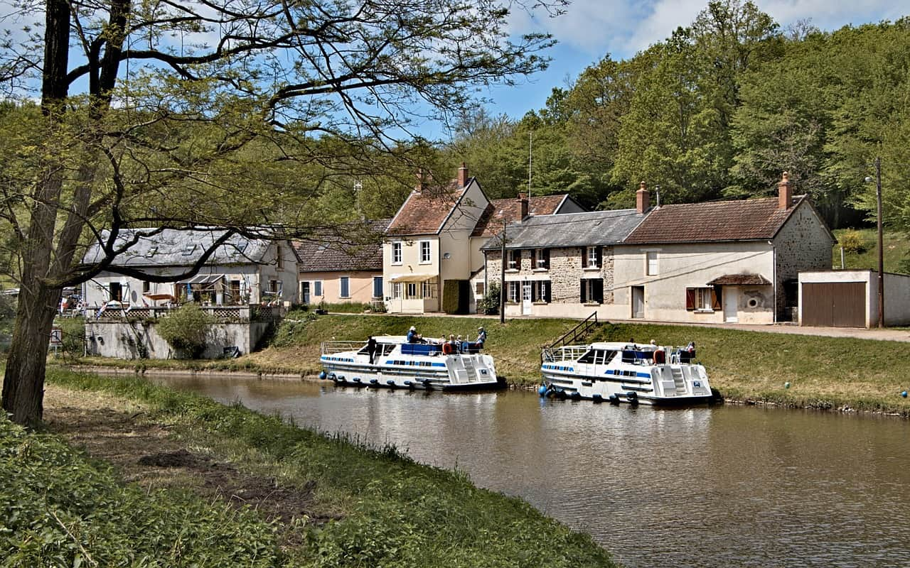 Cruising on a Burgundy canal is one of the most underrated day trips from Paris. This image has two motorboats and a house on the far side of the canal