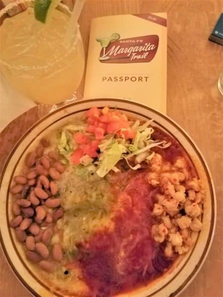 Plate of enchiladas topped with green and red chili. Sides are corn, beans and chopped lettuce & tomato. Margarita Trail Passport and margarita in background.