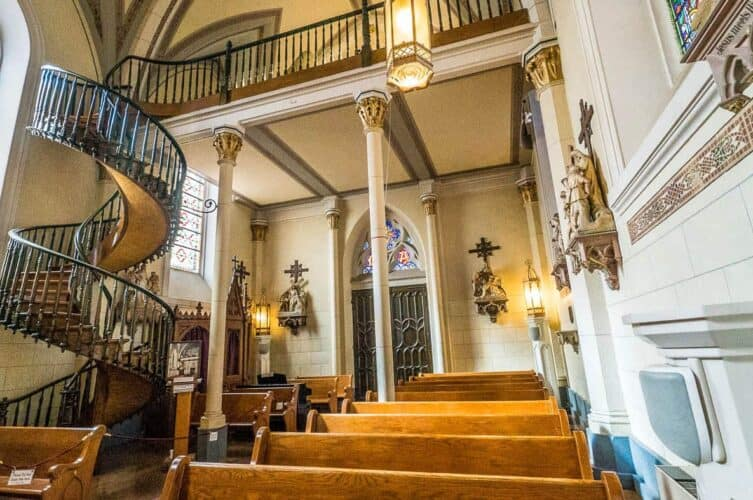 Spiral staircase and pews in the back of Loretto Chapel