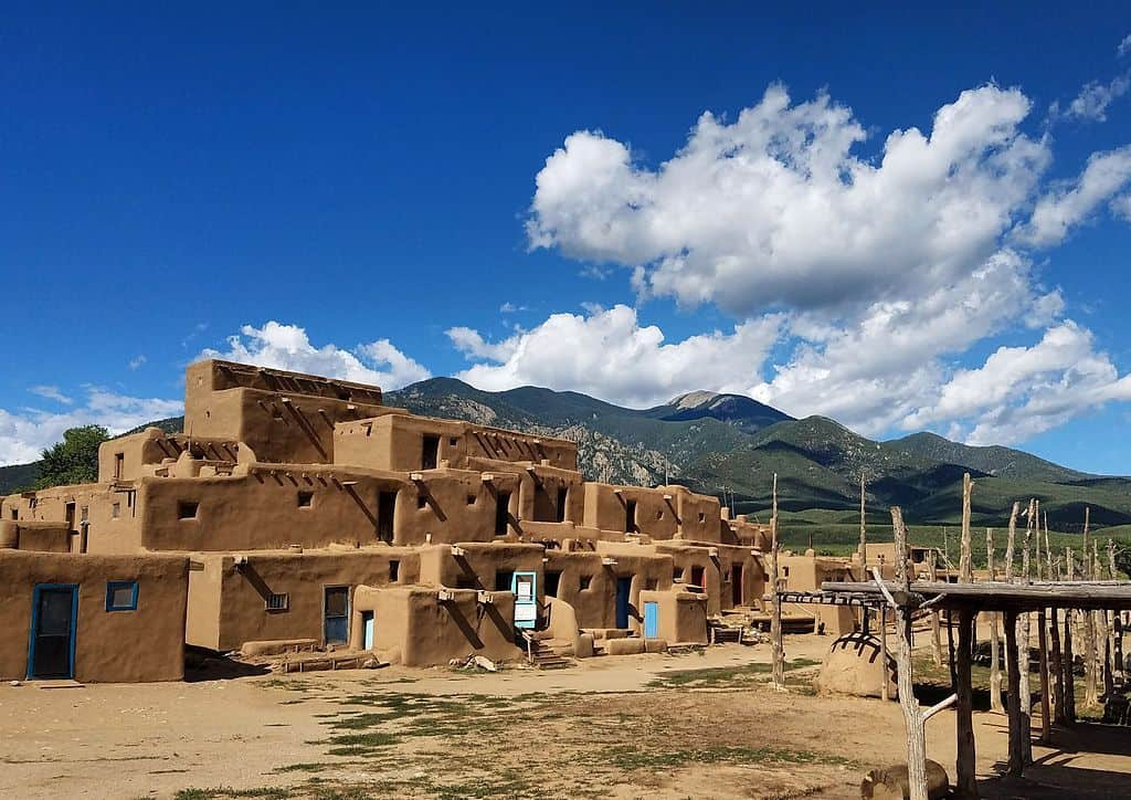 Taos Pueblo framed by mountains and blue sky.