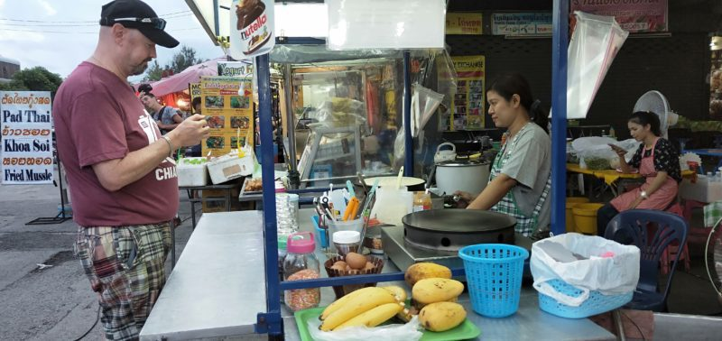 Man buying street food in Chiang Mai Thailand